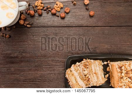 Homemade nut cake with chocolate cream, various nuts and milk on dark wood surface