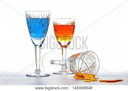 Wineglasses of cut-glass full of colorful liquids over white background