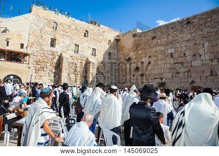 JERUSALEM, ISRAEL - OCTOBER 12, 2014:  Morning autumn Sukkot, Blessing of the Kohanim. The Jews of tallit hold four ritual plants. The area in front of Western Wall of Temple filled with people