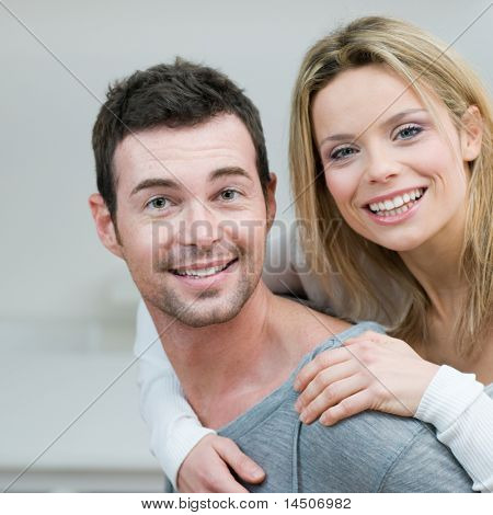 Young couple piggybacking and have fun at home