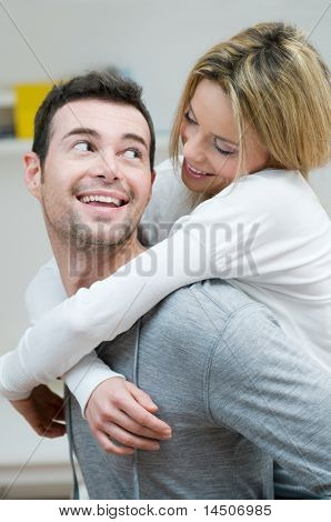Young couple piggybacking and have fun at home with knowing glance