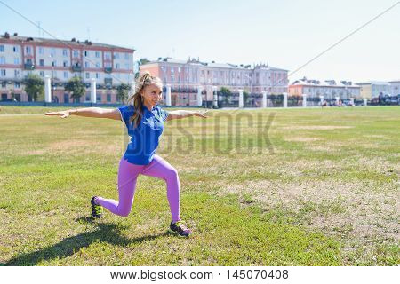 young happy woman doing stretching workout outdoors, yoga pose.