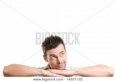 Young smiling man imagine and dreaming looking up at copy space for your text, isolated on white background
