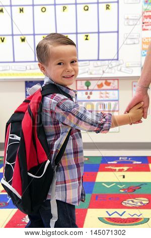 Young boy wearing a backpack, holding his mother's hand in the classroom.