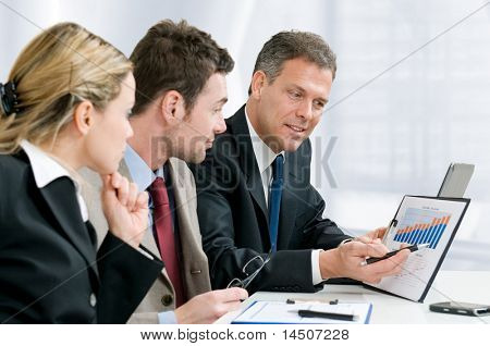 Satisfied senior businessman showing growing chart at his happy colleagues in modern office