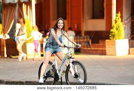 Young beautiful girl riding bicycle on street