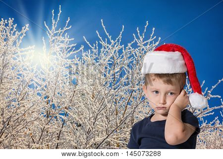 The child has sad blue eyes and fair soft hair. The charming little boy in red cap of Santa Claus. Photo executed on background of snow-covered forest