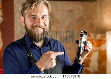 Lviv, Ukraine - August 30, 2016: Smiling sommelier holds Coravin wine system on the brick wall background. Coravin is patented wine system for pouring wine without taking the cork out of the bottle