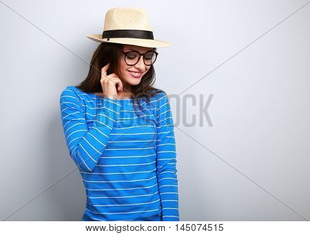 Fun Young Thinking Woman Looking Down In Glasses And Straw Hat On Blue Background