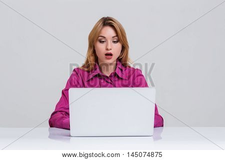 Young businesswoman working at laptop computer. she was surprised, prints and looking at monitor