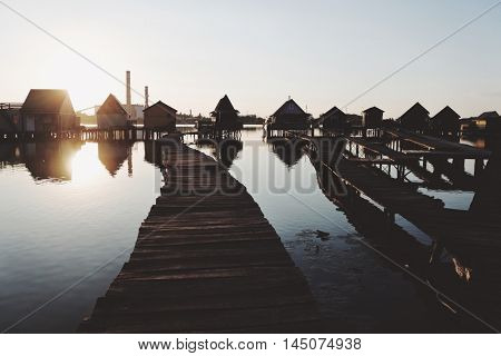 Old wooden pier, and small houses over the lake