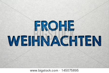 Frohe Weihnachten (Merry Christmas) background card design with textured blue text on a grey background with copy space for your seasonal Christmas greeting