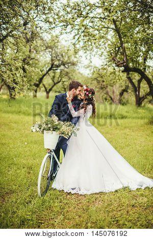 Beautiful bride & groom posing near vintage provence bicycle outdoor