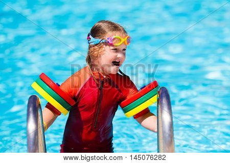 Happy laughing little girl playing in outdoor swimming pool on a hot summer day in sun protection rash guard. Kid in goggles and UV safe bathing suit learning to swim with colorful floaties.