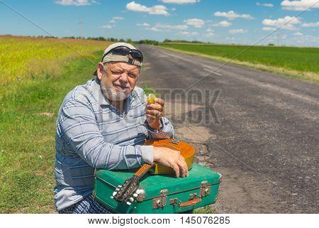 Portrait of senior hiker having short rest on a roadside at summer season