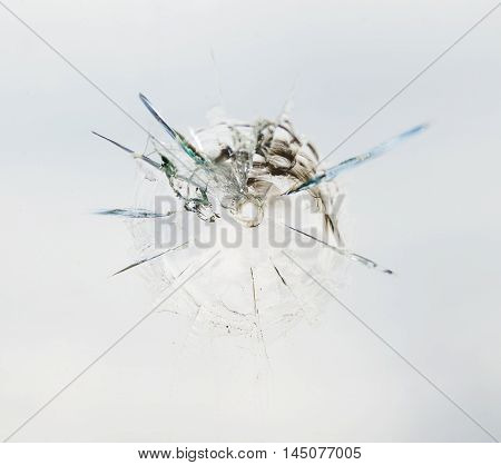 Round bullet hole in the glass with radial cracks
