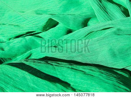 Green fabric abstract background. Chiffon cloth pattern