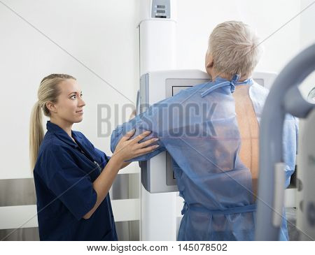 Female Radiologist Taking Chest Xray Of Mature Patient