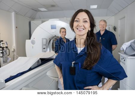Female Radiologist With Colleagues Standing By MRI Machine