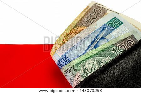 Polish zloty. Many banknotes of different denomination and the polish flag. In the black purse.
