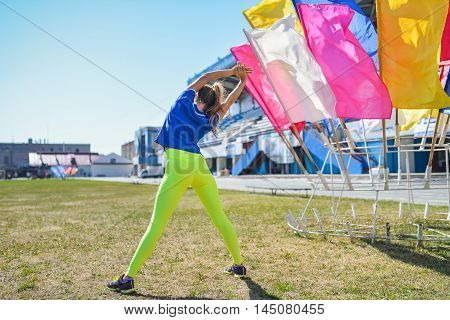 Rear view of fit young Caucasian woman stretching outdoors on sunny summer day.