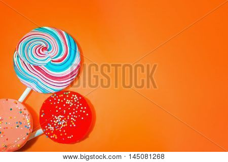 Vintage orange background with three varicolored candy. Space for copy.