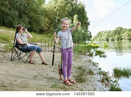 disappointed girl child look on caught fish, grimacing face, people camping and fishing, family active in nature, river and forest, summer season
