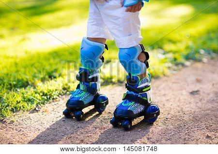 Little boy learning to roller skate in summer park. Children wearing protection pads for safe roller skating ride. Active outdoor sport for kids. Close up view of skates.