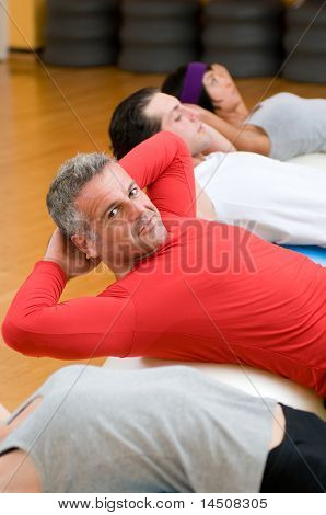 Healthy people with mature instructor doing sit-ups on fitness ball at gym