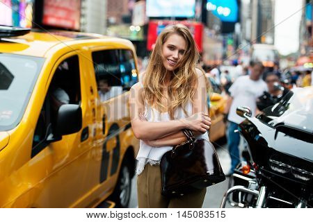 Beautiful fashionable young woman with yellow taxi cab at busy New York City Street. Cheerful blonde girl smiling in the city street and holding bag wearing summer outfit.