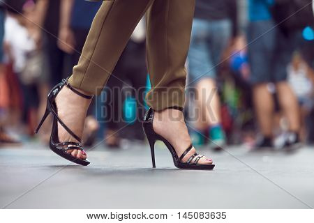 Woman wearing black high heels summer shoes walkin in the city crowd. Woman feet making step on city street. Female legs and feet with shoes close-up.