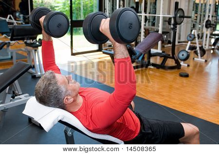 Mature man lifting dumbells at fitness gym, rear view