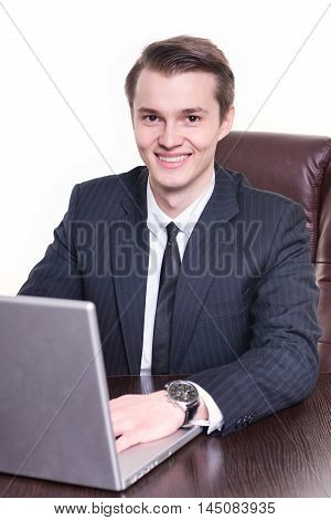 Young happy businessman sitting in the office and working on laptop smilng. Young student man got new ofice job after university.