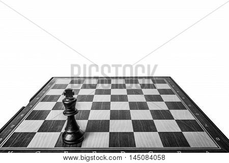 Black chess king deployed on chessboard isolated on white background in black and white