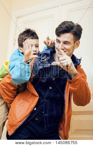 young handsome father with his son fooling around at home, lifestyle real people concept, fathers day