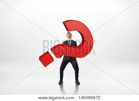 Full portrait of a businessman holding big red 3d question mark isolated on white background. Complicated question. Issues and problems. Troubles at work.