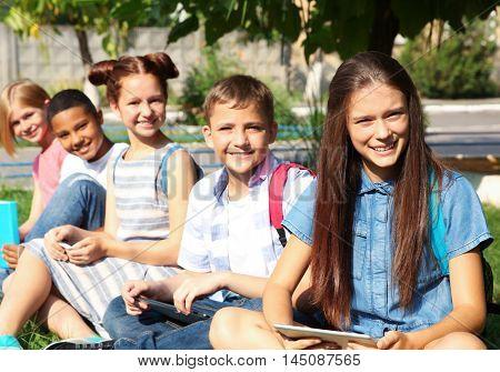 Schoolchildren sitting on grass in schoolyard