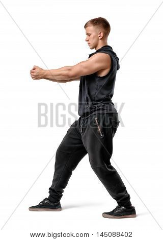 Side view of muscled young man holding something in outstretched arms isolated on white background. Working out at gym. Healthy lifestyle. Bodybuilding.
