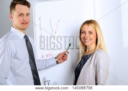 Happy Businessman with businesswoman giving a presentation on flipchart. Teamwork concept