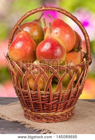 pears in a wicker basket on a wooden table with a blurred background.