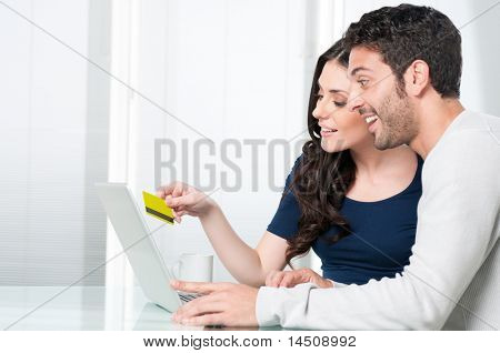 Happy surprised couple looking and buying online with credit card at home