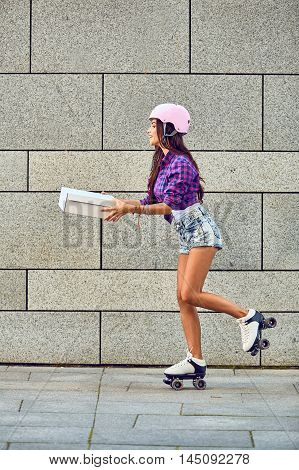 Fast delivery of sportive girl on roller skates. Young woman on roller skates with box or pizza in hands. Brunette beautiful girl delivering box.