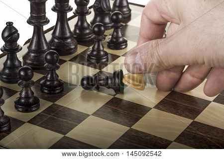 hand that pulls down a black chess figure with a white pawn