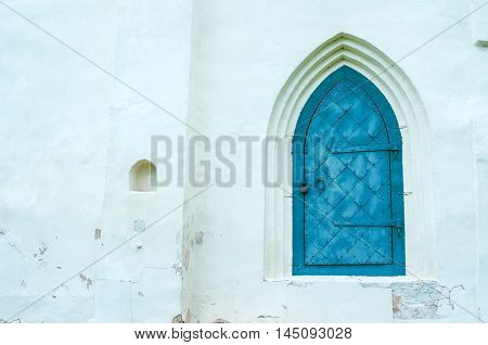 Architecture view of architecture elements- aged dark blue metal forged door with arcade on the white stone wall. Architecture background with architecture details.