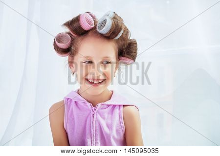 Beautiful little girl with curlers in her hair
