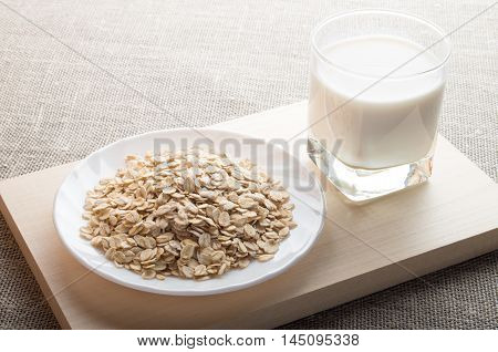 Saucer With Dry Cereal And A Glass Of Milk In The Backlight