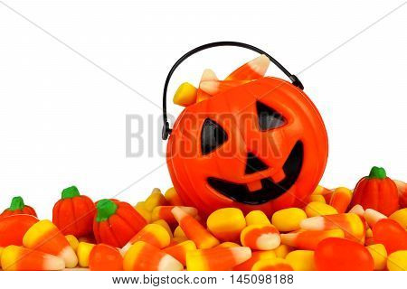Small Halloween Jack O Lantern Pail On A Large Pile Of Candy Over A White Background