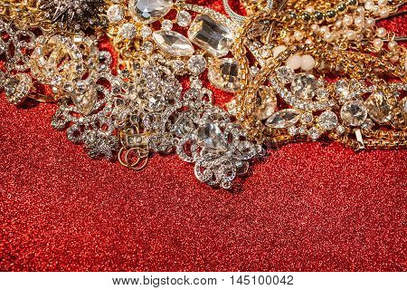 Close up of assorted precious jewelry on red shiny glitter background