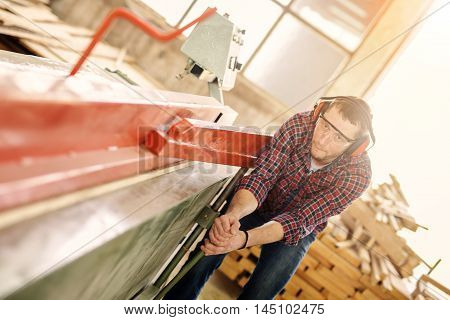 Carpenter with automatic circular saw. He has protective glasses. Holding circular saw with two hands.