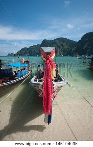 Colourful prayer scarves hang from bows of longtail taxi boats anchored at beach Ao Nang Thailand